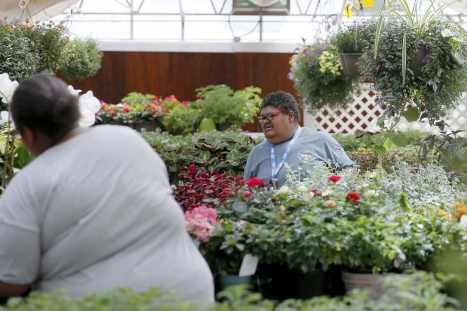 Photo -  Shelly M. works inside a greenhouse at Kristy Lyn's Flowers & Gifts at the Center of Family Love in Okarche. [Bryan Terry/ The Oklahoman]