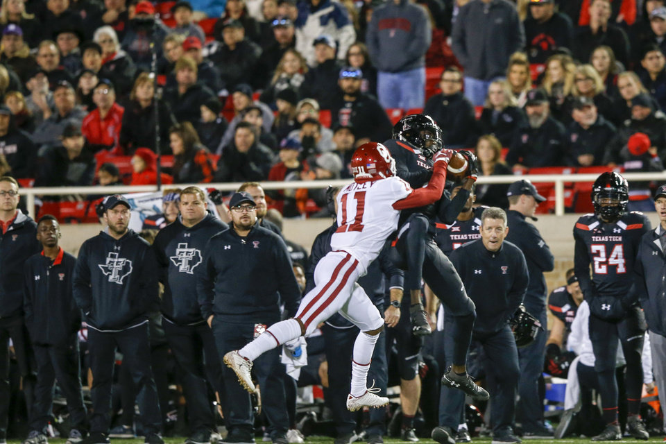 Photo - Oklahoma Sooners cornerback Parnell Motley (11) attempts to knock a pass away from Texas Tech Red Raiders wide receiver T.J. Vasher (9) during the NCAA football game between the Texas Tech Red Raiders and the Oklahoma Sooners at Jones AT&T Stadium in Lubbock, Texas on Saturday, November 03, 2018. IAN MAULE/Tulsa World