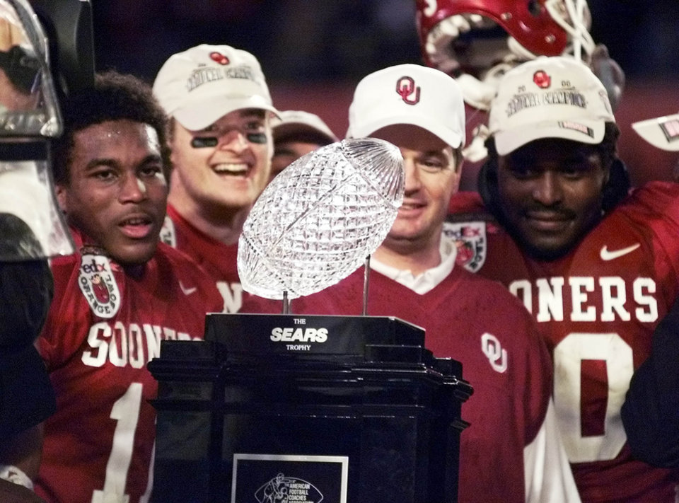 Photo - NATIONAL CHAMPIONSHIP, ORANGE BOWL, OU VS. FLORIDA STATE COLLEGE FOOTBALL: SEARS NATIONAL CHAMPIONSHIP TROPHY BEING ADMIRED BY OU HEAD COACH BOB STOOPS (IN SWEATER) AND QUARTERBACK JOSH HEUPEL AT HIS RIGHT AND FELLOW TEAMMATES.