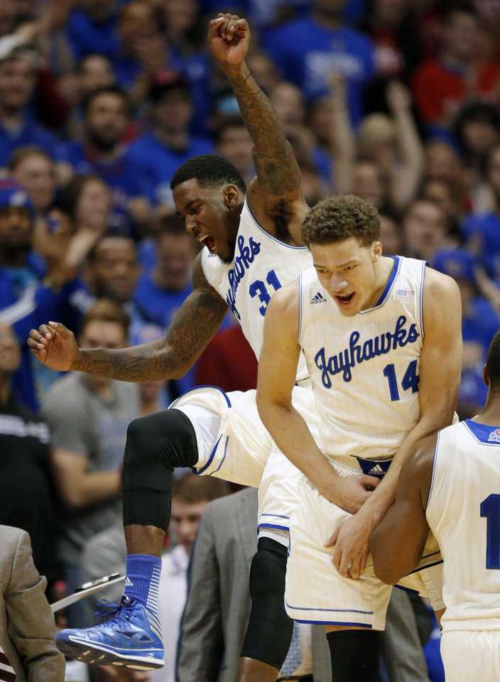 Photo - Kansas forward Jamari Traylor (31) and guard Brannen Greene (14) celebrate at a timeout during the first half of an NCAA college basketball game against Oklahoma State at Allen Fieldhouse in Lawrence, Kan., Saturday, Jan. 18, 2014. (AP Photo/Orlin Wagner)
