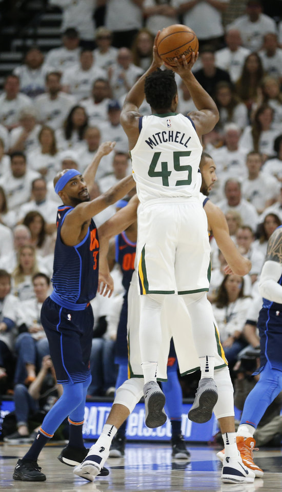 Photo - Utah Jazz guard Donovan Mitchell (45) shoots as Oklahoma City Thunder forward Corey Brewer (3) defends in the first half during Game 4 of an NBA basketball first-round playoff series Monday, April 23, 2018, in Salt Lake City. (AP Photo/Rick Bowmer)