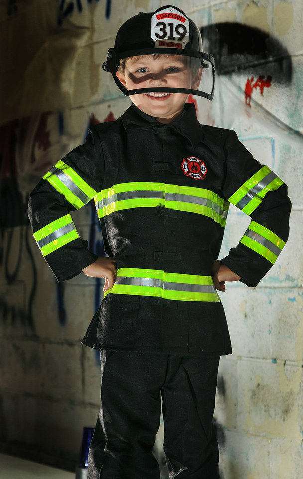 Photo - Blake is ready to fight the biggest fire dressed as a junior firefighter.  This costume comes with a coat with reflective lining, pants and shielded helmet. Costume from Party Galaxy.  Photo by Chris Landsberger, The Oklahoman  CHRIS LANDSBERGER
