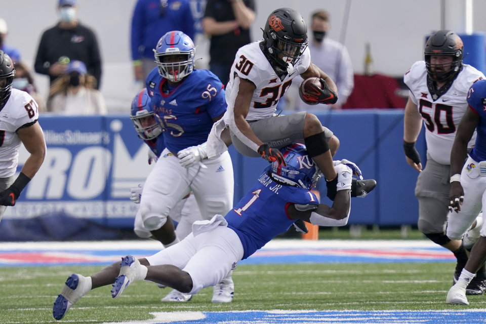 Photo - Oklahoma State running back Chuba Hubbard (30) is tackled by Kansas cornerback Kenny Logan Jr. (1) during the first half of an NCAA college football game in Lawrence, Kan., Saturday, Oct. 3, 2020. (AP Photo/Orlin Wagner)