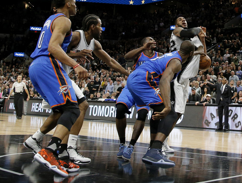 Photo - Oklahoma City's Serge Ibaka (9) knocks th ball away from San Antonio's LaMarcus Aldridge (12) in the final moments of Game 2 of the second-round series between the Oklahoma City Thunder and the San Antonio Spurs in the NBA playoffs at the AT&T Center in San Antonio, Monday, May 2, 2016. Oklahoma City won 98-97. Photo by Bryan Terry, The Oklahoman