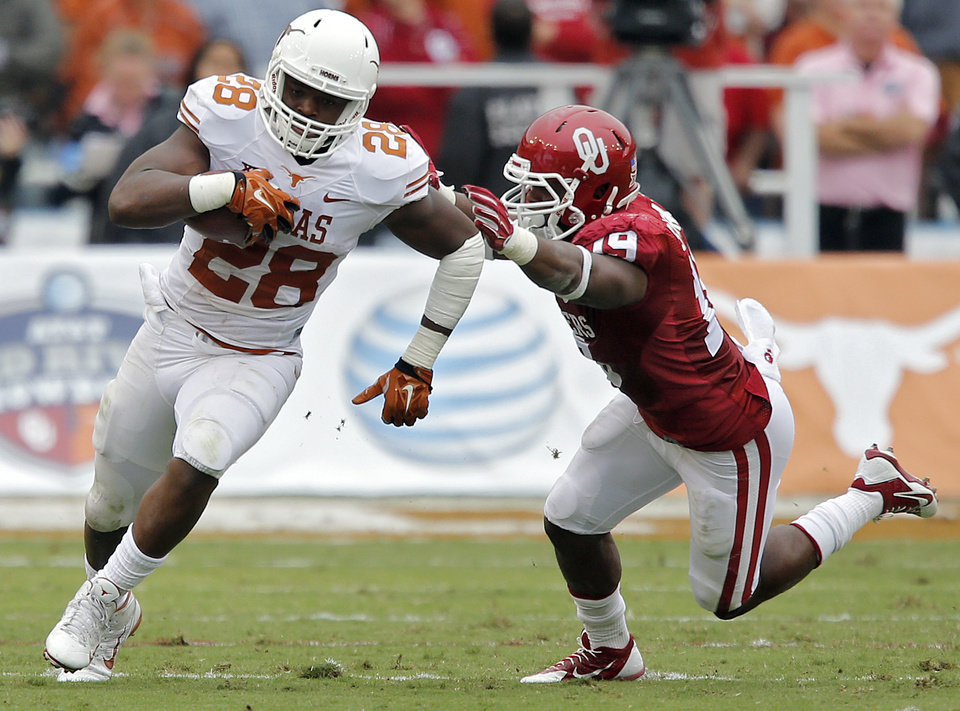 Photo - Oklahoma's Eric Striker (19) tries to stop Texas' Malcolm Brown (28) during the college football game between the University of Oklahoma Sooners (OU) and the University of Texas Longhorns (UT) during the Red River Showdown at the Cotton bowl in Dallas, Texas on Saturday, Oct. 11, 2014. Photo by Chris Landsberger, The Oklahoman