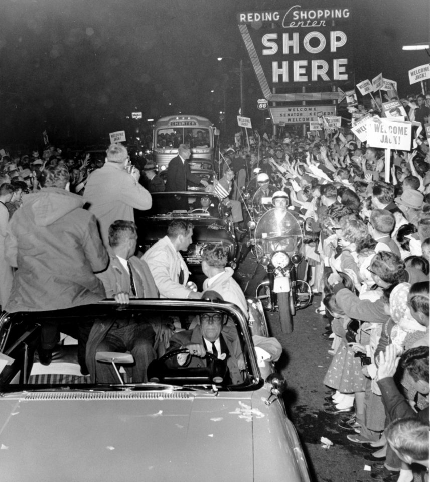 Photo - STATE, OKLAHOMA, CAMPAIGN, VISIT, VISITS, REDING SHOPPING CENTER: Democratic presidential nominee John F. Kennedy stands up in his car and acknowledges the crowd as his motorcade passes through the intersection of SW 44 and Western on its way to a Democratic rally at the Municipal Auditorium in downtown Oklahoma City. Senator Kennedy made a last-minute, whirlwind stop in Oklahoma City just before the 1960 elections. Staff photo by Jim Lucas taken 11/3/60; photo ran in the 11/4/60 Oklahoma City Times Late Street edition.