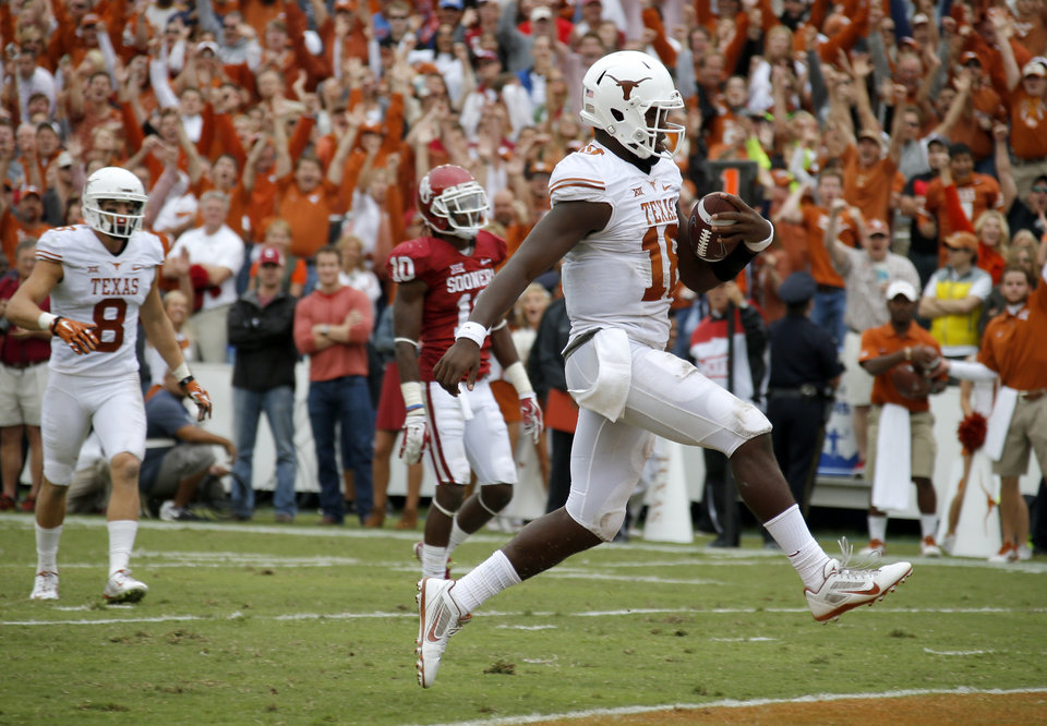 Photo - Texas' Tyrone Swoopes (18) scores a touchdown during the Red River Showdown college football game between the University of Oklahoma Sooners (OU) and the University of Texas Longhorns (UT) at the Cotton Bowl in Dallas on Saturday, Oct. 11, 2014. 