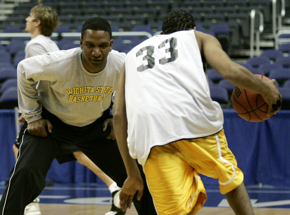 Photo - Wichita State assistant coach Alvin Williamson guards Sean Ogirri (33) during practice at the Verizon Center in Washingon, Thursday, March 23, 2006. Wichita State faces George Mason in the third round of the NCAA basketball tournament on Friday. (AP Photo/Lawrence Jackson)