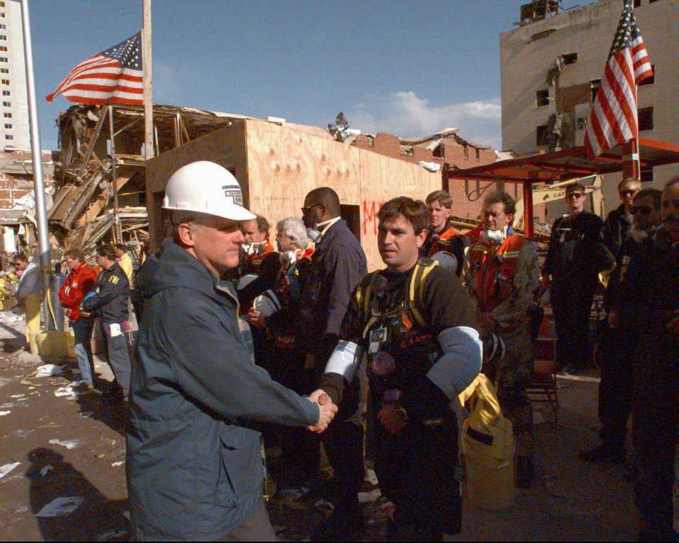 Photo -  Oklahoma Gov. Frank Keating, left, shakes hands with rescue workers in downtown Oklahoma City on April 26, 1995, in the bombed-out area of the city. The governor joined rescue crews in  a moment of silence at 9:02 a.m. in rememberance of those killed in bombing one week earlier of the Alfred P. Murrah Federal Building. [David Longstreath/AP file Photo]