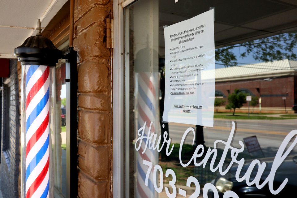 Photo - Sign in the window of Hair Central lets customers know about the new rules in Moore, Monday, April 27, 2020.  [Doug Hoke/The Oklahoman]