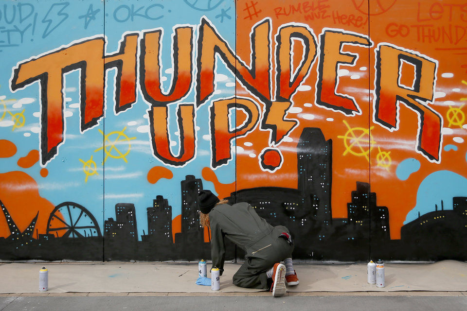 Photo - Artist Tony Thunder finishes a painting outside the arena before an NBA basketball game between the Oklahoma City Thunder and the Sacramento Kings at Chesapeake Energy Arena in Oklahoma City, Sunday, Oct. 21, 2018. Photo by Bryan Terry, The Oklahoman