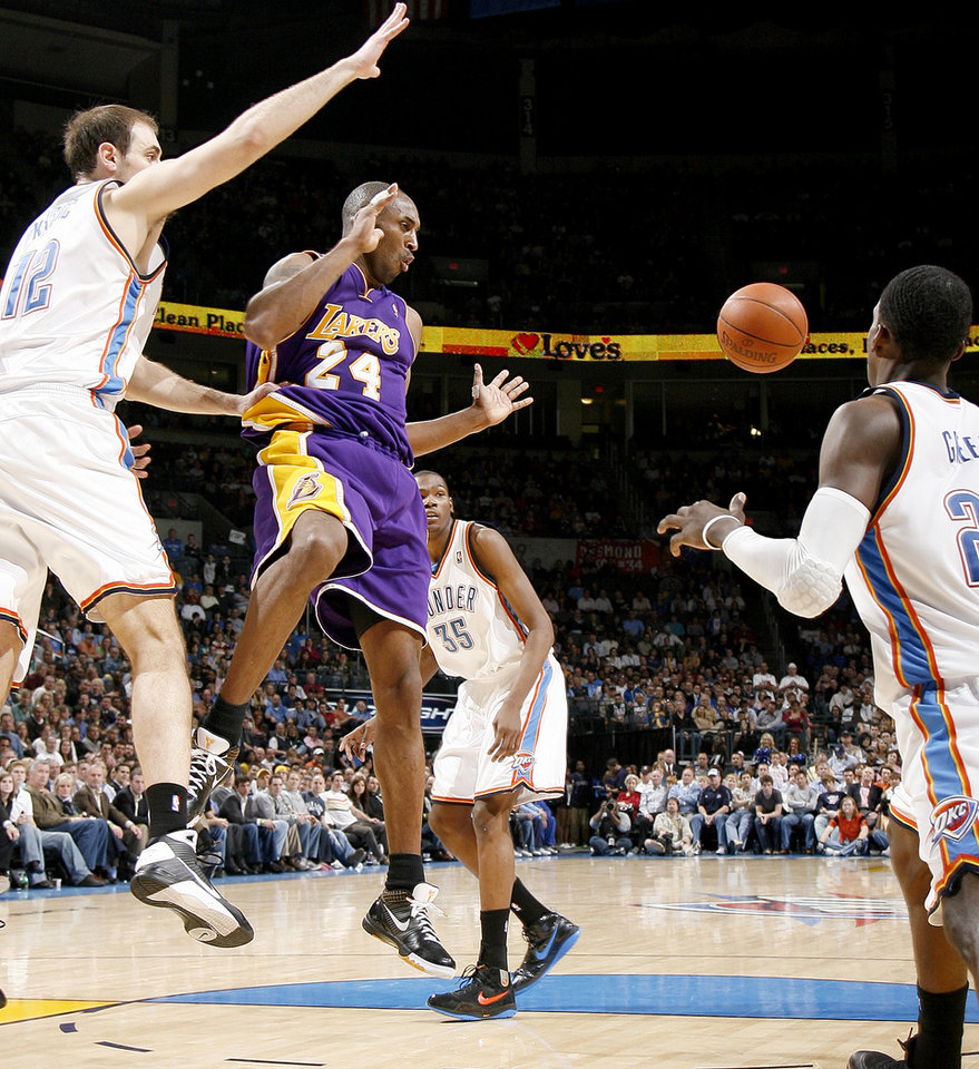 Photo - Kobe Bryant of the Lakers passes the ball between Oklahoma City's Nenad Krstic, left, Kevin Durant and Jeff Green during the NBA basketball game between the Los Angeles Lakers and the Oklahoma City Thunder at the Ford Center,Tuesday, Feb. 24, 2009. The Thunder lost 107-93. 