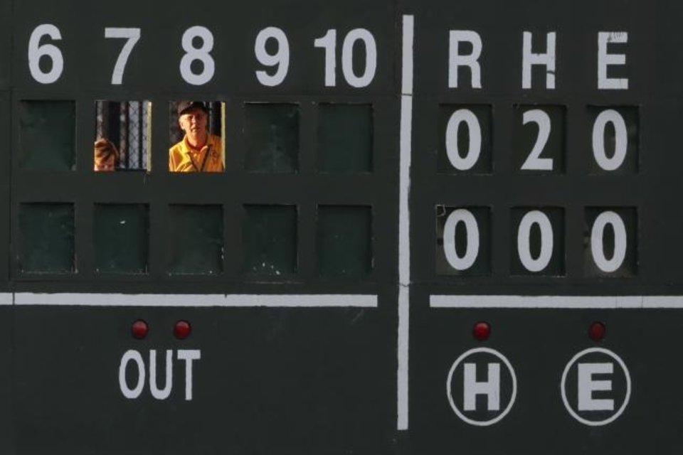 Photo -  Scoreboard operators look from behind run slots during the second inning of the Atlantic League All-Star minor league baseball game on July 10, 2019, in York, Pa. [AP Photo/Julio Cortez]