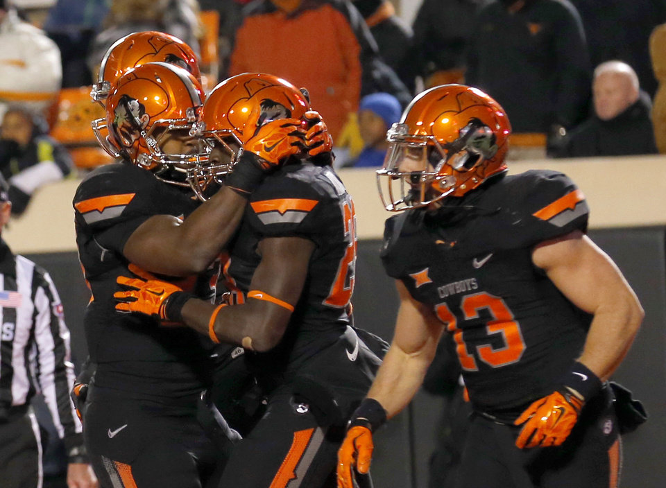 Photo - Oklahoma State celebrates a James Washington (28) (middle) touchdown in the fourth quarter during the college football game between the Oklahoma State University Cowboys (OSU) the University of Texas Longhorns (UT) at Boone Pickens Staduim in Stillwater, Okla. on Saturday, Nov. 15, 2014.  Photo by Sarah Phipps, The Oklahoman