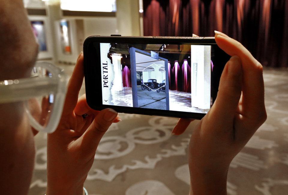 Photo -  Kenna Jackson with Trifecta Communications demonstrates an augmented reality scavenger hunt app on a smartphone at the 21C Hotel. [Photo by Steve Sisney, The Oklahoman]