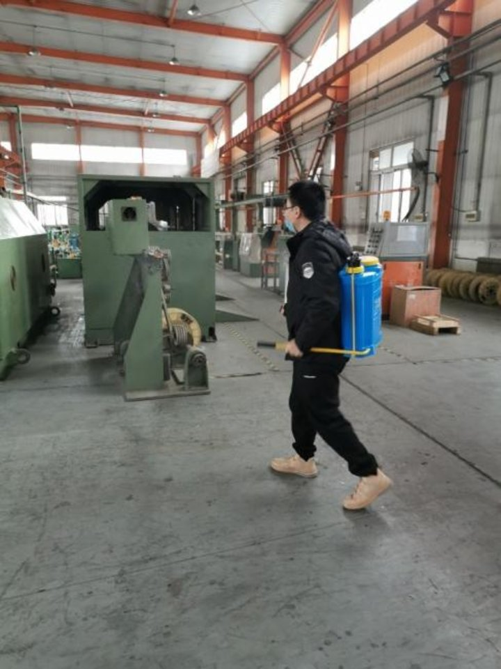 Photo -  An employee at Dynamic Tehnologies in Hebei, China, sprays sanitizing mist around the property. The factory is a manufacturing partner with Oklahoma City-based R.T. Clark Co. [PHOTO PROVIDED]