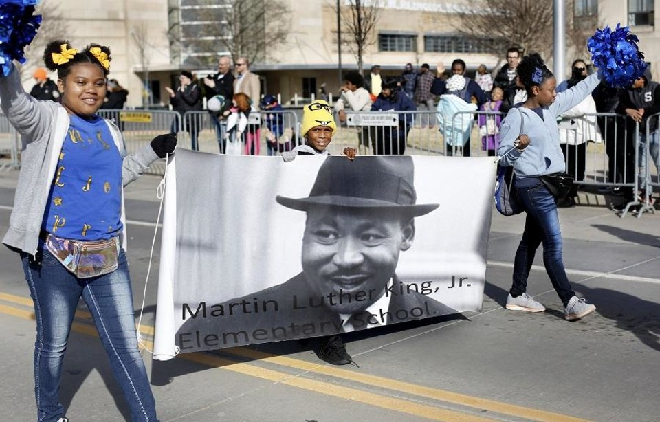 Photo - Children carry a banner representing their school, named for the famed civil rights leader, during the Martin Luther King, Jr. Day Parade as it passes along city streets in downtown Oklahoma City on Monday afternoon, Jan. 21, 2019. [The Oklahoman Archives photo]