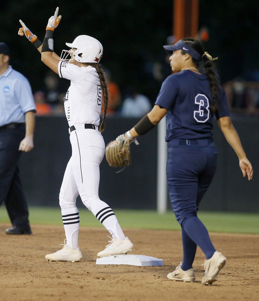 Photo - Oklahoma State's Kiley Naomi (5) celebrates in front of BYU's Marissa Chavez (3) after hitting a double in the third inning of the Stillwater Regional NCAA softball tournament game between Oklahoma State (OSU) and BYU in Stillwater, Okla., Thursday, May 16, 2019. Oklahoma State won 3-1. [Bryan Terry/The Oklahoman]