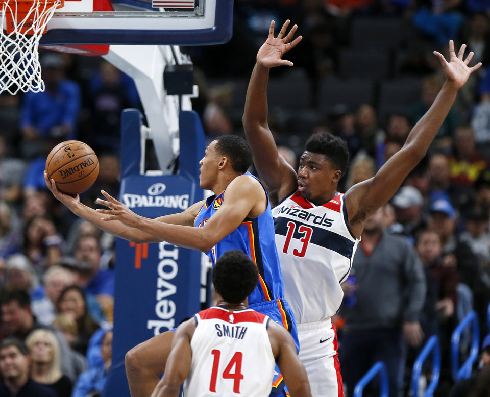 Photo - Oklahoma City's Darius Bazley (7) takes the ball to the basket between Washington's Thomas Bryant (13) and Ish Smith (14) in the third quarter during an NBA basketball game between the Oklahoma City Thunder and the Washington Wizards at Chesapeake Energy Arena in Oklahoma City, Friday, Oct. 25, 2019. The Wizards won 97-85. [Nate Billings/The Oklahoman]