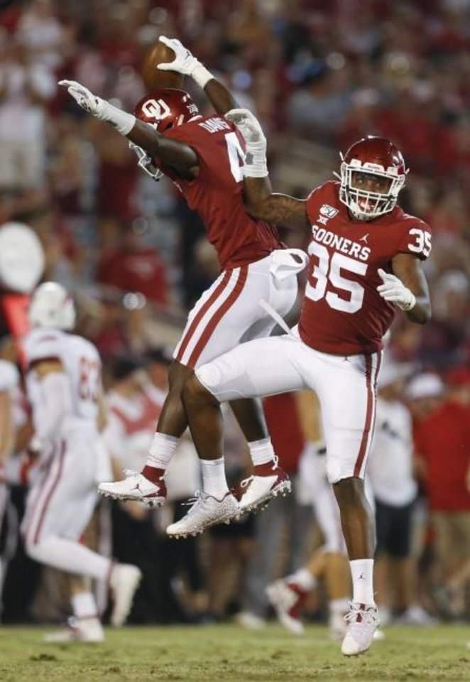 Photo -  Oklahoma's Jaden Davis, left, and Nik Bonitto celebrate after an interception by Davis in the fourth quarter of the Sept. 7 win over South Dakota. [Nate Billings/The Oklahoman]
