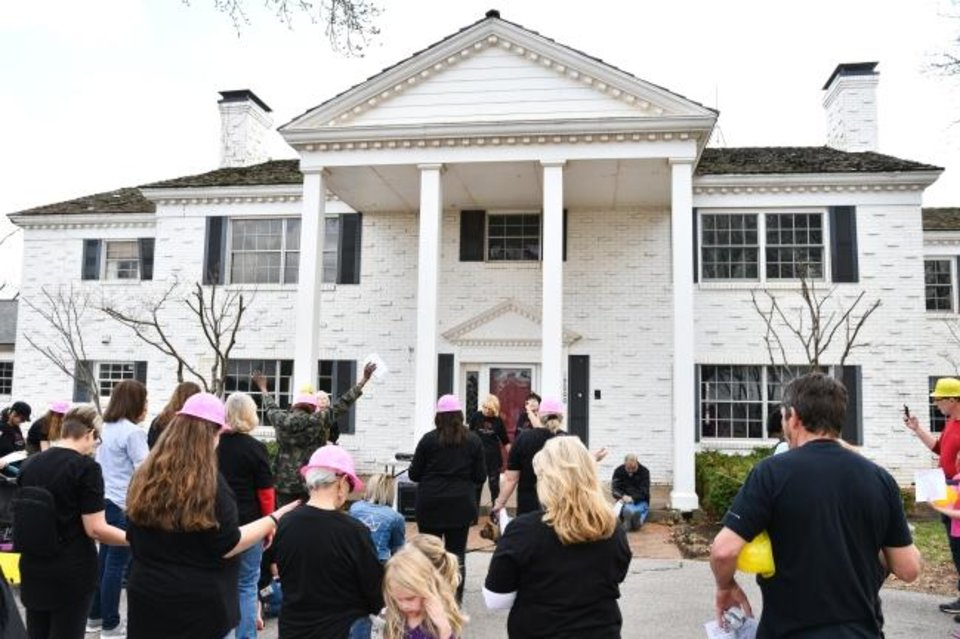 Photo -  Beautiful Restoration participants and supporters gather around a house dubbed