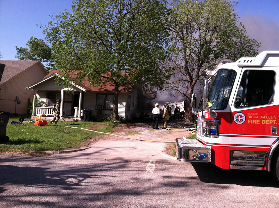 Photo - Firefighters battle a house fire at 3009 NW 20 in Oklahoma City Sunday.  TIFFANY GIBSON - THE OKLAHOMAN