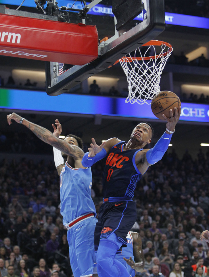 Photo -  Oklahoma City Thunder guard Russell Westbrook drives to the basket past Sacramento Kings center Willie Cauley- Stein during Monday's basketball game in Sacramento, Calif. [AP Photo]