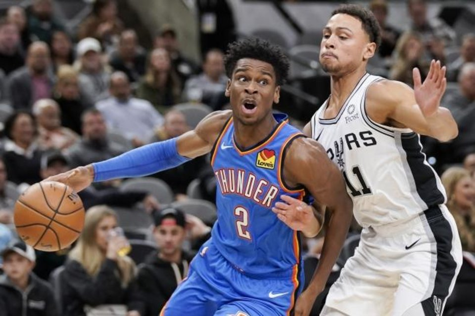 Photo -  Oklahoma City's Shai Gilgeous-Alexander, left, drives against San Antonio's Bryn Forbes during the first half of Thursday night's game at AT&T Center in San Antonio. [AP Photo/Darren Abate]