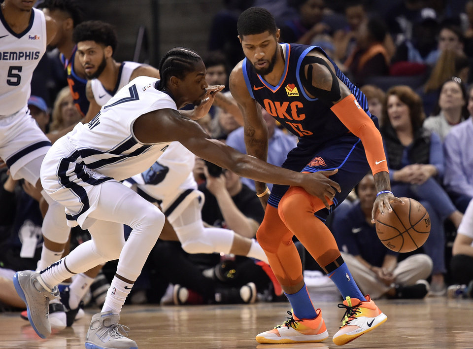 Photo - Oklahoma City Thunder forward Paul George (13) handles the ball against Memphis Grizzlies forward Justin Holiday (7) during the first half of an NBA basketball game Monday, March 25, 2019, in Memphis, Tenn. (AP Photo/Brandon Dill)