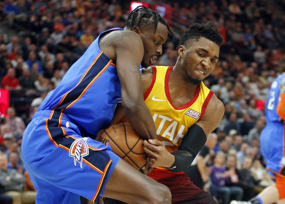 Photo - Oklahoma City Thunder forward Jerami Grant, left, and Utah Jazz guard Donovan Mitchell, right, battle for the ball in the first half during an NBA basketball game Monday, March 11, 2019, in Kearns, Utah. (AP Photo/Rick Bowmer)