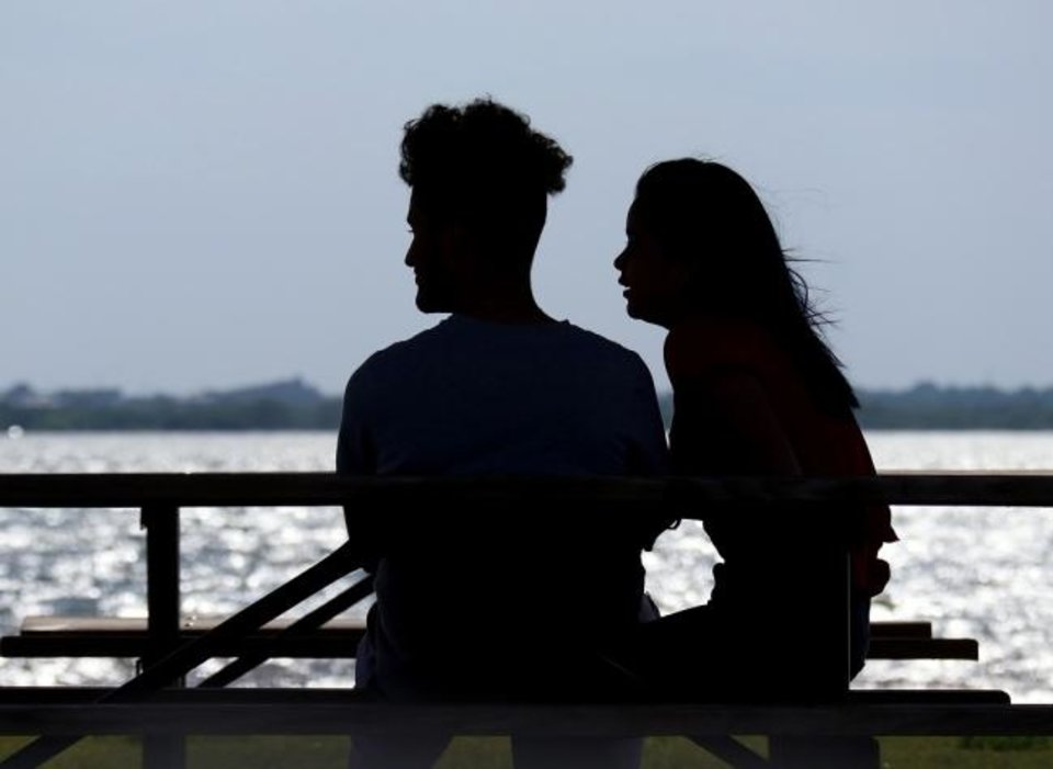 Photo -  A couple sit in the shade at a picnic table on April 27 and watch sail surfers enjoy the windy conditions at Lake Hefner.  [Doug Hoke/The Oklahoman Archives]