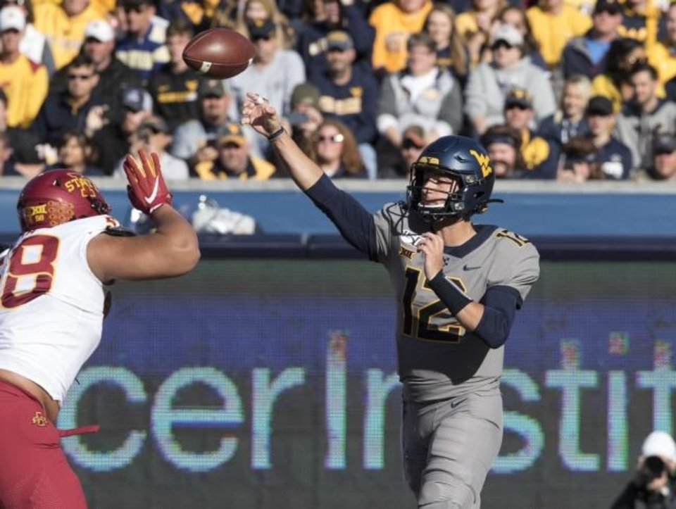 Photo -  Former Oklahoma quarterback Austin Kendall, right, throws a pass during last Saturday's West Virginia-Iowa State game in Morgantown, W.Va. Kendall transferred to West Virginia in January and is the Mountaineers' starter. [AP Photo/Raymond Thompson]