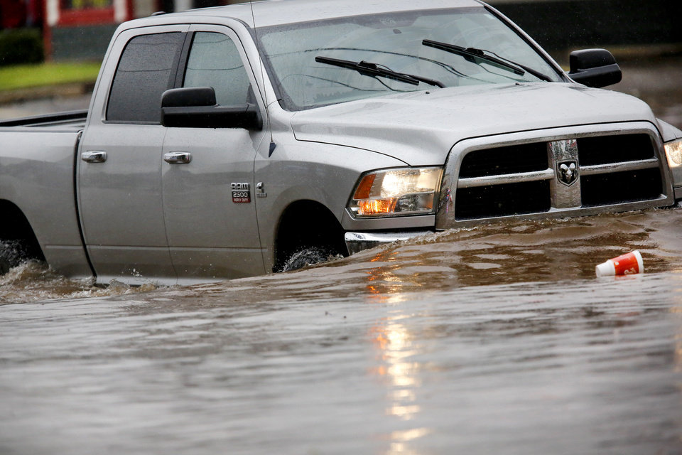 Photo - A large truck fords high water on SW 29 Street Thursday, June 6, 2019, when heavy rains overwhelmed stormwater drainage systems and flooded streets, requiring  high water rescues in Oklahoma City as another round of severe storms passes through the metro.