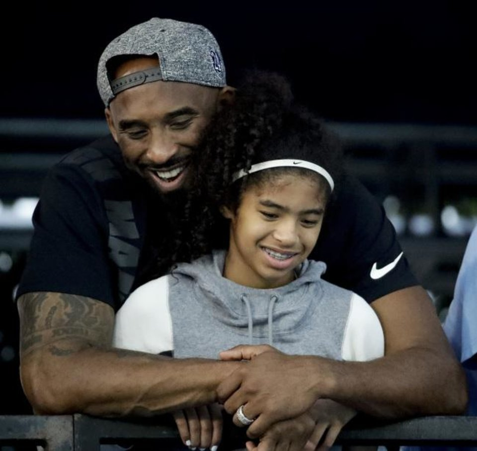Photo -  Former Los Angeles Laker Kobe Bryant and his daughter Gianna watch a swimming meet in 2018. Bryant, 41, and his 13-year-old daughter both died in a helicopter crash Sunday. [Chris Carlson/The Associated Press]