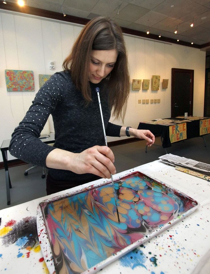 Photo - Kerri Shadid, an artist and poet, demonstrates techniques for marbling paper, Friday, December 12, 2014, at the Skirvin Hilton Hotel. [The Oklahoman Archives]