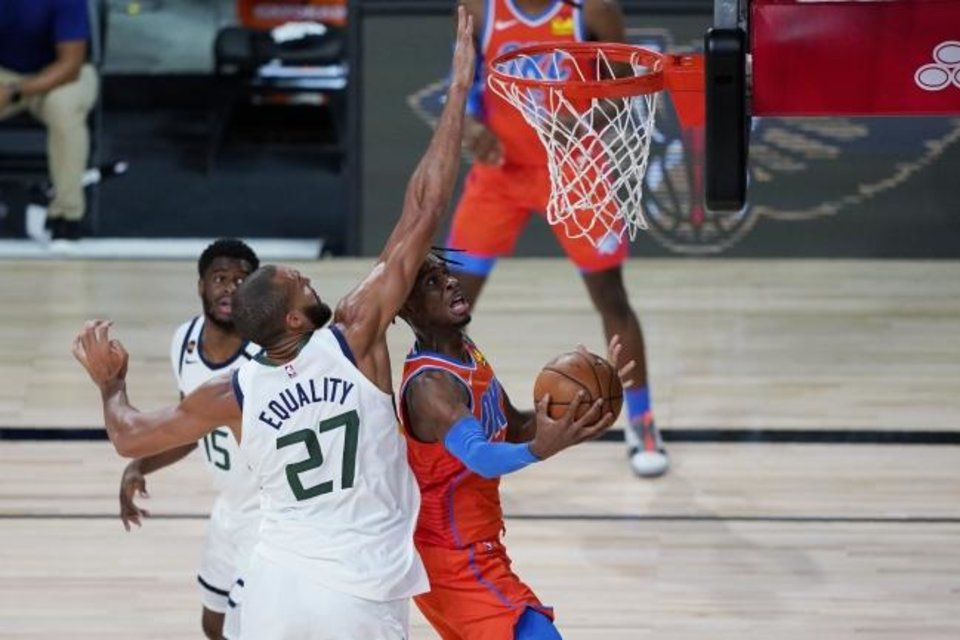 Photo -  Thunder guard Shai Gilgeous-Alexander, who scored 19 points Saturday, shoots around Jazz center Rudy Gobert (27) during the first half. [AP Photo/Ashley Landis, Pool]