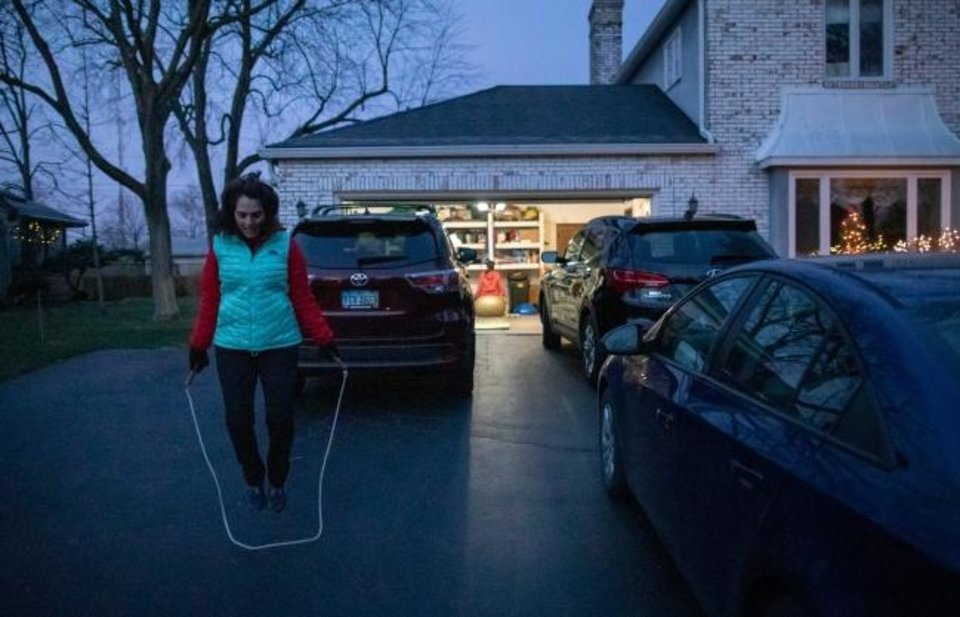Photo -  Olga Stavridis, 53, jump ropes in the driveway of her neighbor Donna Reda's Upper Arlington, Ohio, house, while working out with personal trainer Caitlin Kennelly on Dec. 15. [Adam Cairns/Columbus Dispatch/TNS]
