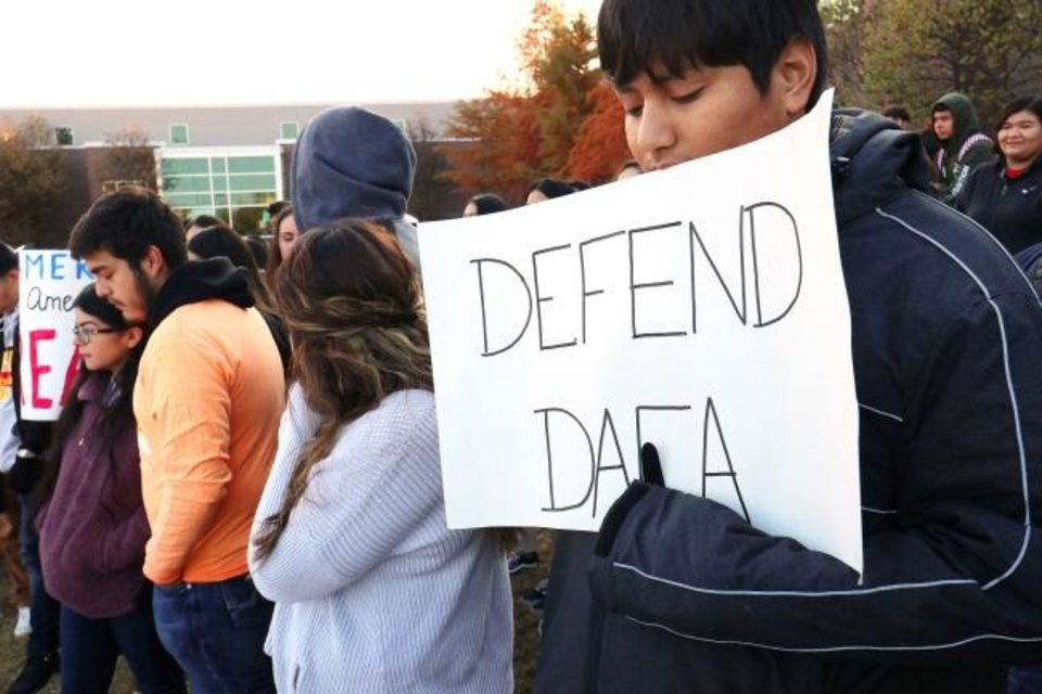 Photo -  Senior Uriel Salazar holds a defend DACA sign at U.S. Grant High School during a student walkout supporting the immigration program on Friday. [Doug Hoke/The Oklahoman]