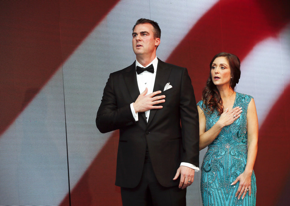 Photo - Gov. Kevin Stitt and first lady Sarah Stitt say the Pledge of Allegiance during the inaugural ball for Stitt at the Cox Convention Center in Oklahoma City, Monday, Jan. 14, 2019. Photo by Nate Billings, The Oklahoman