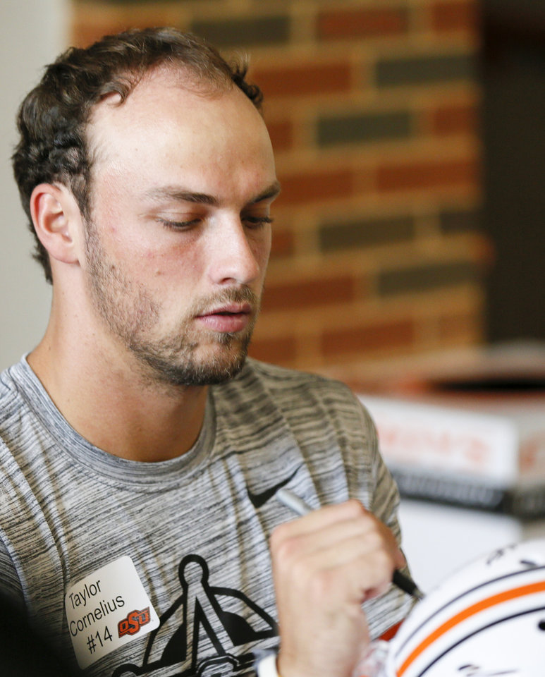 Photo -  OSU quarterback Taylor Cornelius signs a helmet during Fan Appreciation Day last weekend. [PHOTO BY NATE BILLINGS, THE OKLAHOMAN]