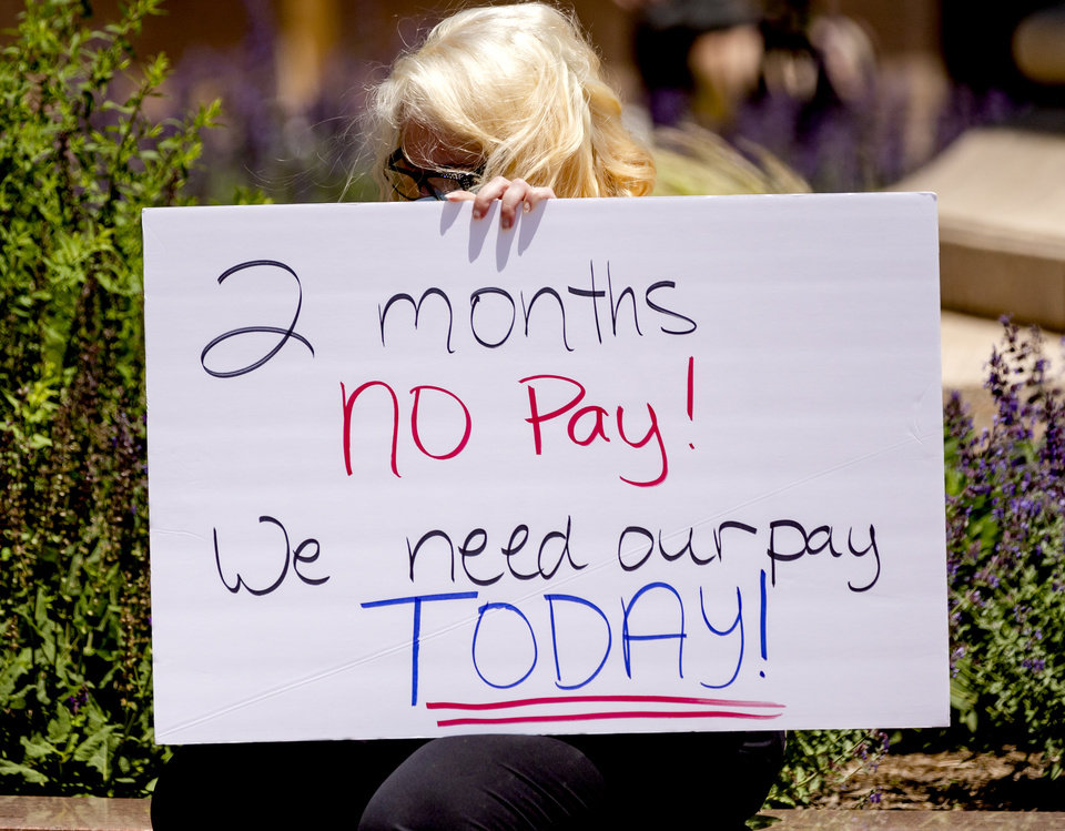 Photo - A protester carries a sign while gathering with other self-employed Oklahomans at the Oklahoma state Capitol to protest the lack of unemployment payments on Monday, May 18, 2020, in Oklahoma City, Okla..  [Chris Landsberger/The Oklahoman]