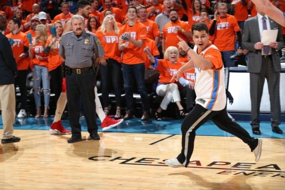 Photo -  Derek Williamson runs across the court at Chesapeake Energy Arena after making a half-court shot for $20,000 during a Friday playoff game between the Oklahoma City Thunder and the Portland Trailblazers. (Photo by Zach Beeker/NBAE via Getty Images)