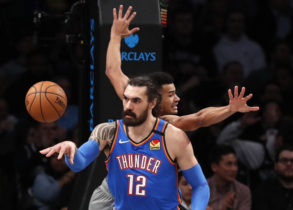 Photo - Oklahoma City Thunder guard Andre Roberson (21) passes after grabbing a rebound in front of Brooklyn Nets guard Timothe Luwawu-Cabarrot, right, during the first half of an NBA basketball game, Tuesday, Jan. 7, 2020, in New York. (AP Photo/Kathy Willens)