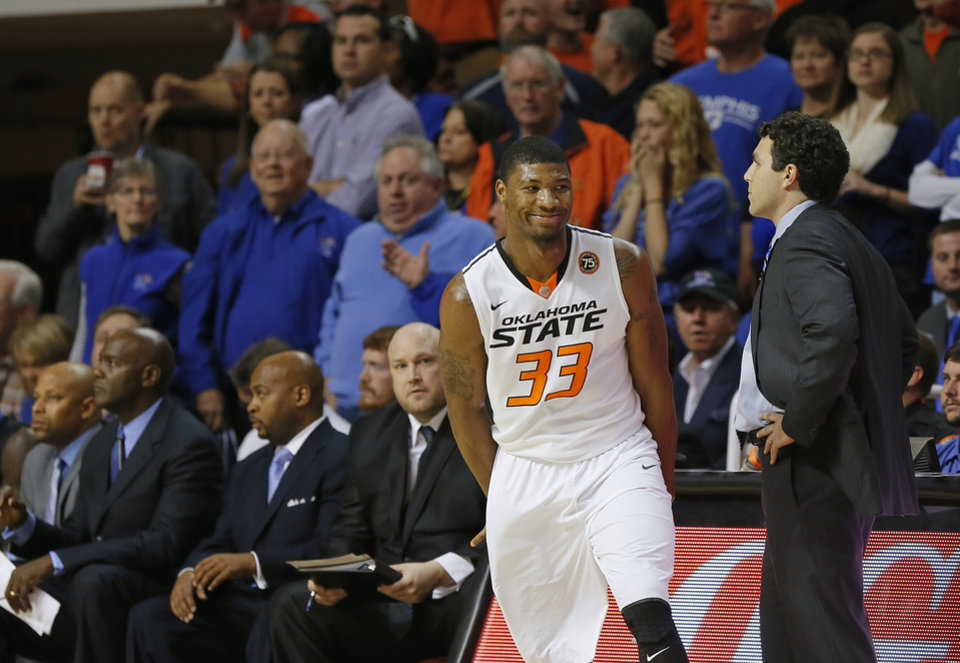 Photo - Oklahoma State's Marcus Smart (33) smiles as he runs past Memphis coach Josh Pastner after making a basket during the first half of an NCAA college basketball game between Oklahoma State and Memphis at Gallagher-Iba Arena in Stillwater, Okla., Tuesday, Nov. 19, 2013. Photo by Bryan Terry, The Oklahoman