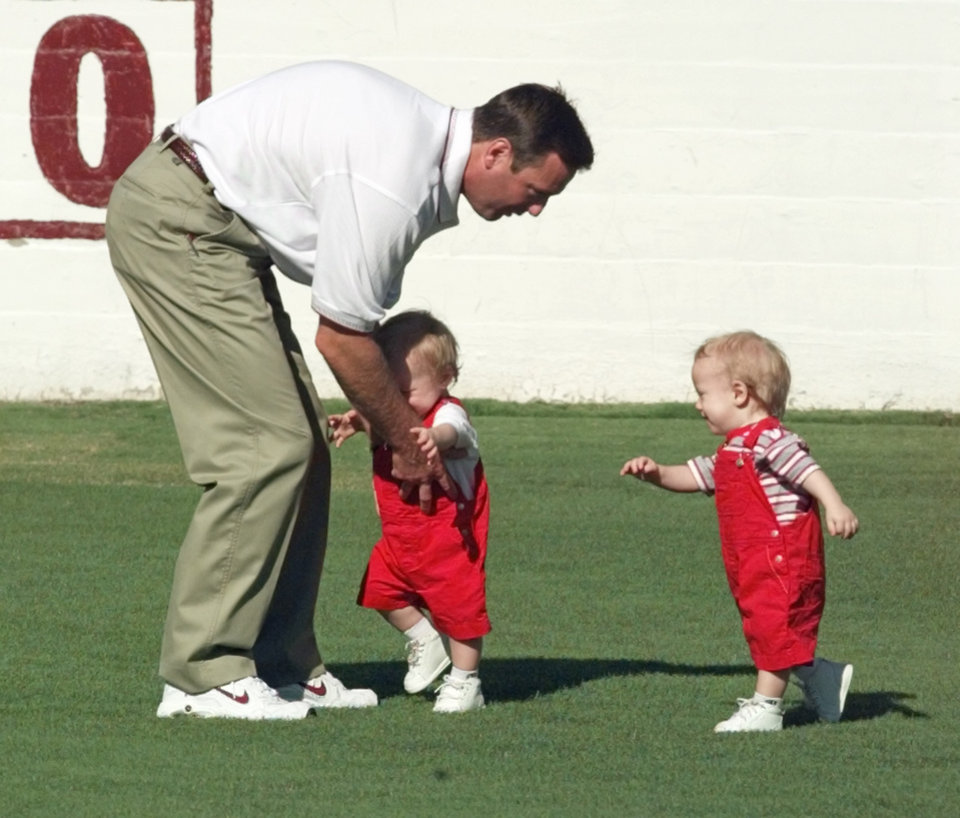 Photo - University of Oklahoma head football coach Bob Stoops plays with his twin sons Isaac and Drake on Owen Field Wednesday during OU media - fan appreciation day.