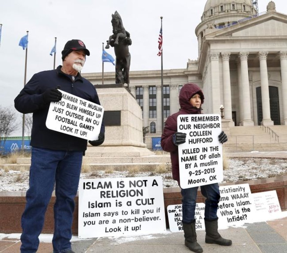 Photo - More than 100 participated in Muslim Day at the Capitol on Monday, March 4, 2019.  The annual event is sponsored by the Council on American-Islamic Relations-Oklahoma chapter. Interfaith supporters   held signs welcoming Muslim guests as they arrived at the Capitol. A man and a woman stood nearby, displaying placards expressing concerns about crimes committed by some Muslims in the recent past.   Photo by Jim Beckel, The Oklahoman.