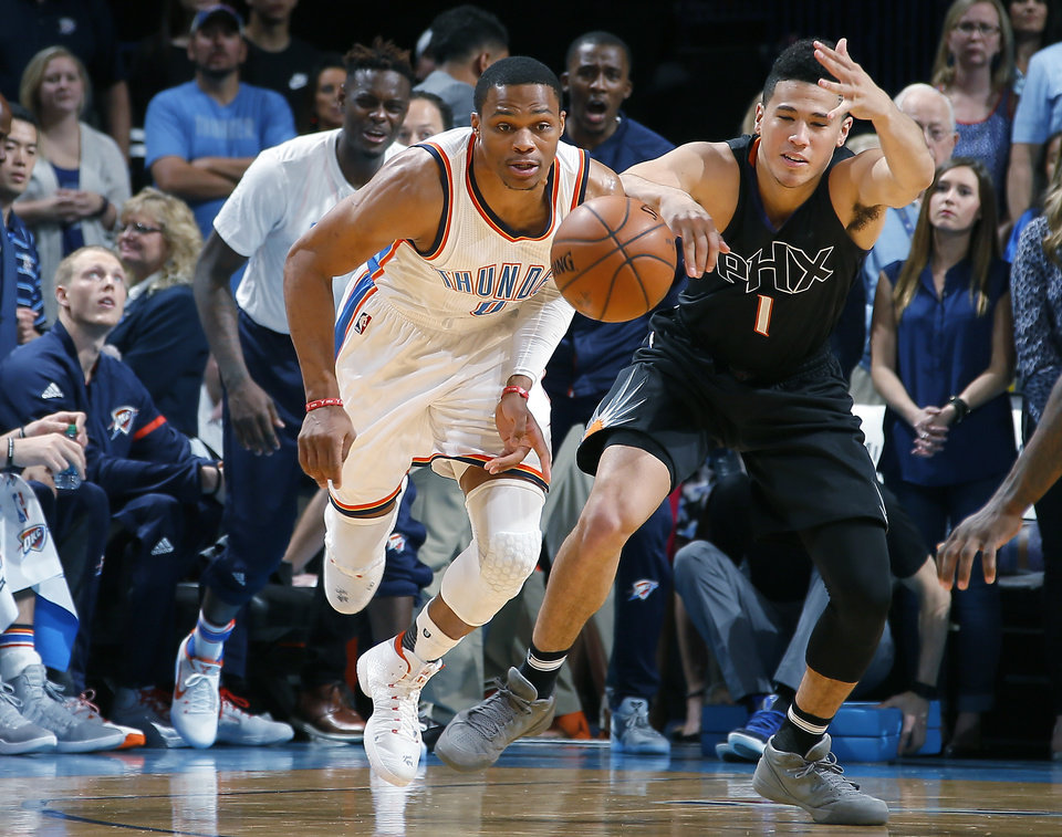 Photo - Oklahoma City's Russell Westbrook (0) goes for the ball beside Phoenix's Devin Booker (1) during an NBA basketball game between the Oklahoma City Thunder and the Phoenix Suns at Chesapeake Energy Arena in Oklahoma City, Friday, Oct. 28, 2016. Photo by Bryan Terry, The Oklahoman