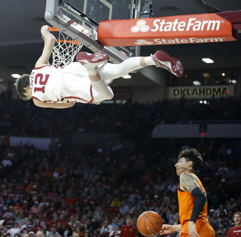 Photo - Oklahoma's Austin Reaves (12) hangs on the rim over Oklahoma State's Lindy Waters III (21) after a dunk during a Bedlam college basketball game between the University Oklahoma Sooners (OU) and the Oklahoma State Cowboys (OSU) at the Lloyd Noble Center in Norman, Okla., Saturday, Feb. 1, 2020. Oklahoma won 82-69. [Bryan Terry/The Oklahoman]