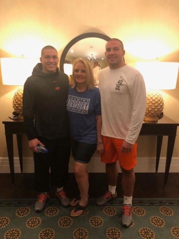 Photo -  Oklahoma State linebacker Malcolm Rodriguez, left, and defensive end Brock Martin, right, pose with Penny Martin. Brock and Rodriguez shaved their heads for Penny, who was diagnosed with cancer last month. [Photo provided]