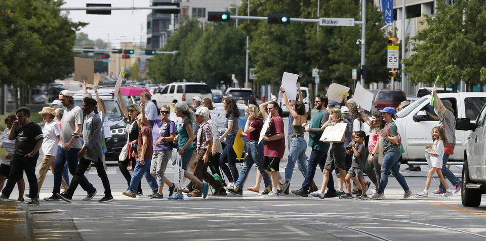 Photo - People cross Sheridan Ave. as they march south on Hudson Ave. during the Oklahoma City Climate Strike event, part of global rallies and marches to bring attention to climate change, in Oklahoma City, Friday, Sept. 20, 2019. [Nate Billings/The Oklahoman]